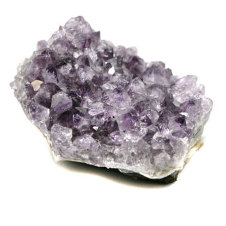 A deep purple amethyst crystal cluster from Uruguay against a white background