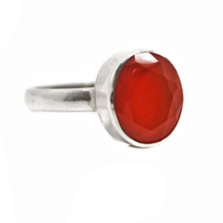 A sterling silver ring featuring a faceted deep orange carnelian stone against a white background