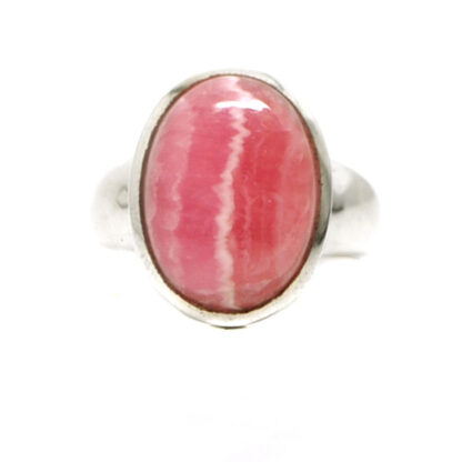 A vibrant pink rhodochrosite oval shaped cabochon set into a simple sterling silver ring against a white background