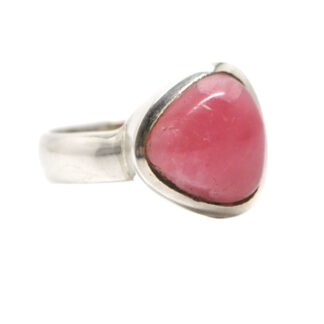 A vibrant pink rhodochrosite triangular shaped cabochon set into a simple sterling silver ring against a white background