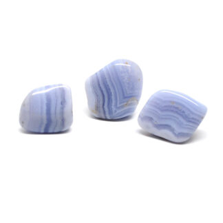 A set of three blue lace agate tumbled stones against a white background