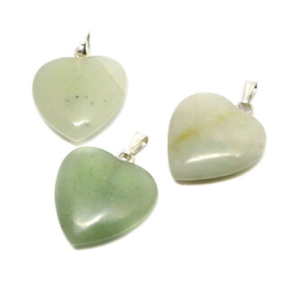 Three small light green jade carved heart pendants against a white background