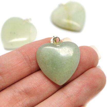 A hand holding a small light green jade carved heart pendant against a white background