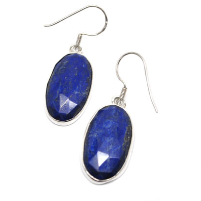 A pair of oval lapis lazuli sterling silver earrings against a white background