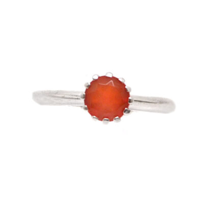 A faceted carnelian set into a sterling silver ring with a crown bezel against a white background