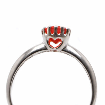 """A faceted carnelian set into a sterling silver ring with a crown bezel and heart """"window"""" accent against a white background"""