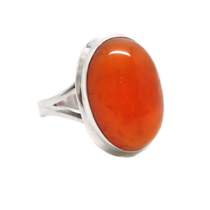 A vibrant oval carnelian cabochon set into a sterling silver ring against a white background