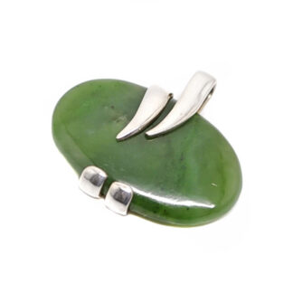 An oval dark green jade cabochon set into a wrapped style sterling silver pendant against a white background