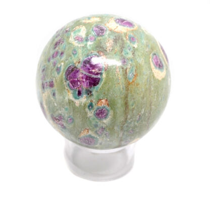 A fuchsite sphere with ruby crystal inclusions against a white background