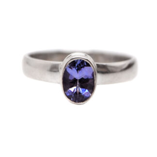 An oval faceted tanzanite gemstone set into a simple sterling silver ring against a white background