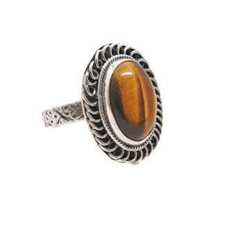 An oval tiger's eye cabochon set into a decorative sterling silver ring with a textured band and roped bezel against a white background