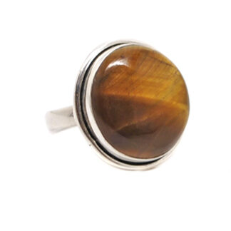 An oval tiger's eye cabochon set into a simple sterling silver ring against a white background