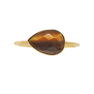A teardrop tiger's eye faceted gemstone set into a dainty vermeil ring against a white background