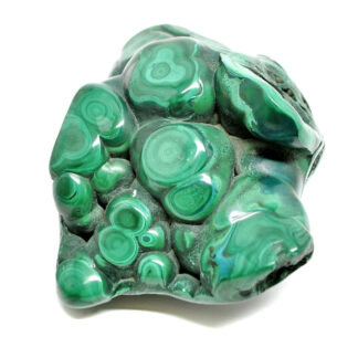 A polished free form green malachite specimen with defined banding against a white background