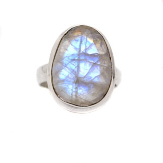 An oval rainbow moonstone cabochon set into a simple sterling silver ring against a white background